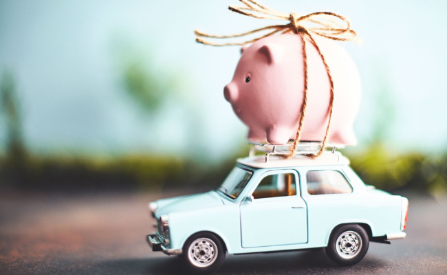 Piggy bank attached to the top of a toy car